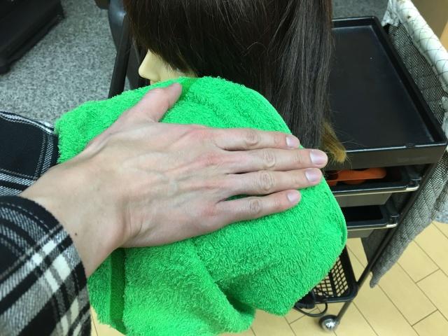 髪の毛をタオルで挟んで手で叩く写真