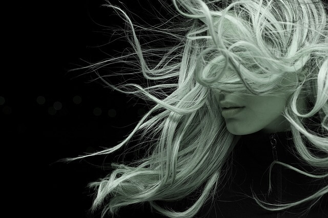 風に吹かれる女性の写真