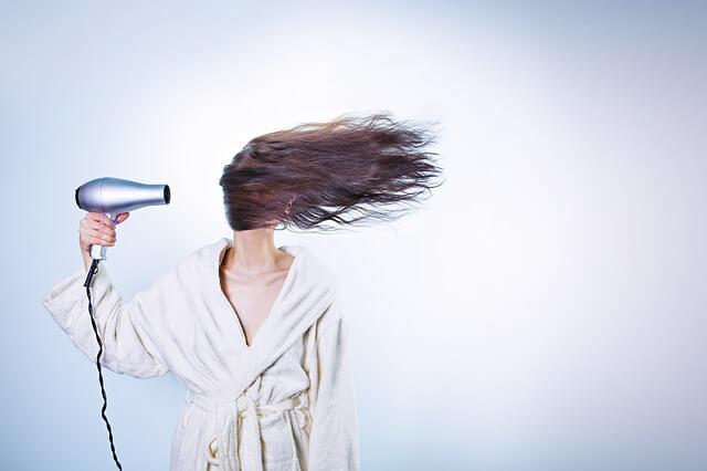 ドライヤーで髪を乾かす女性の写真