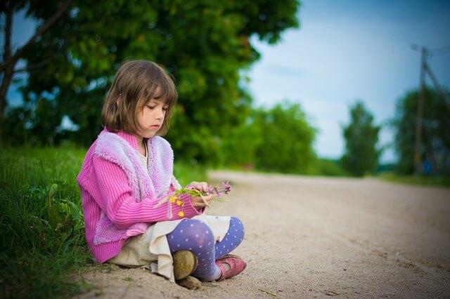 花を見つめる女の子の写真
