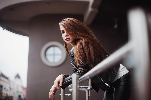 コチラを見つめる髪色のあかるい女性の写真