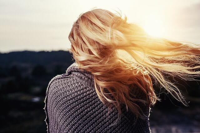 風に吹かれている女性の写真