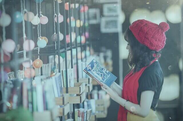 本を読む巻き髪の女性の写真