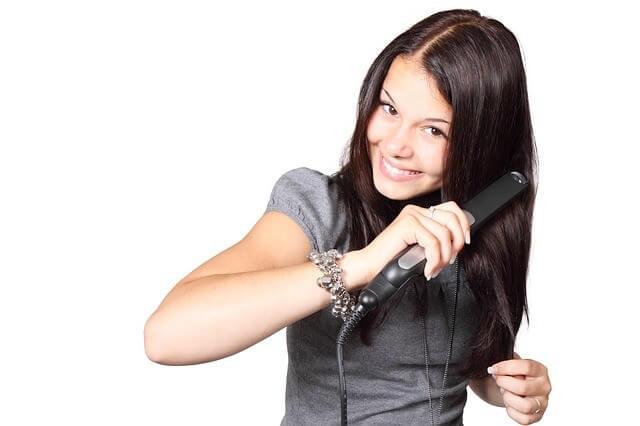 ストレートアイロンで髪の毛を伸ばす女性の写真