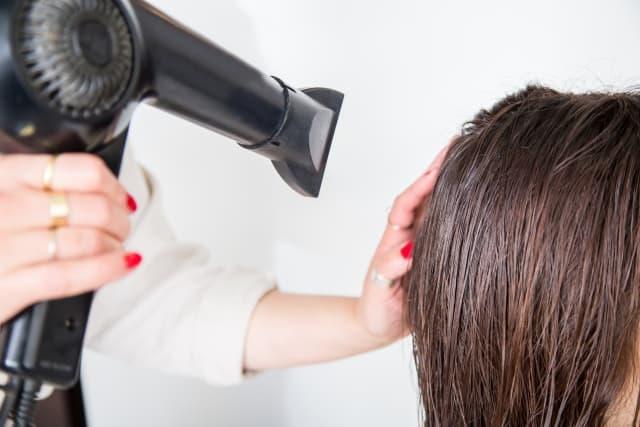 ドライヤーで髪を乾かしている