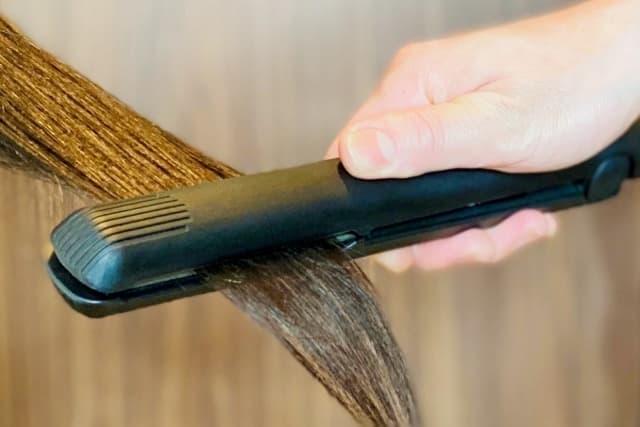ヘアアイロンで髪を伸ばしている
