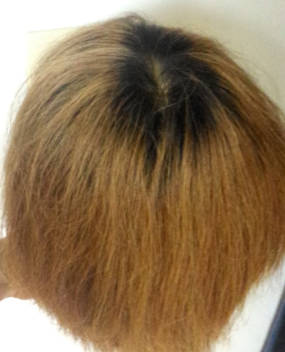 根元が伸びて黒くなっている髪の毛の写真