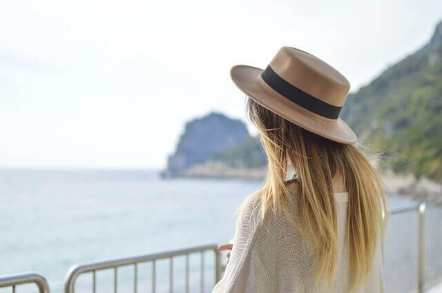 海で帽子を被る女性の写真