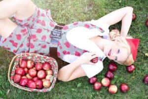 リンゴの横に横たわる女性の写真