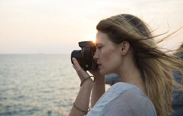海で写真を撮る女性