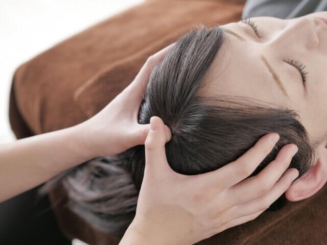 頭をマッサージされる女性