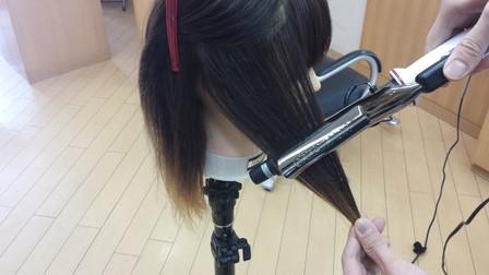 髪の毛をコテで巻いている写真