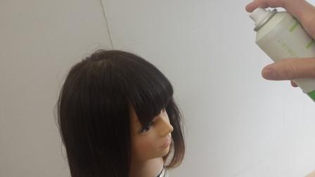 前髪にスプレーをかけている写真