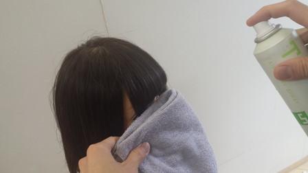 前髪にスプレーが付かないようにタオルを使っている写真