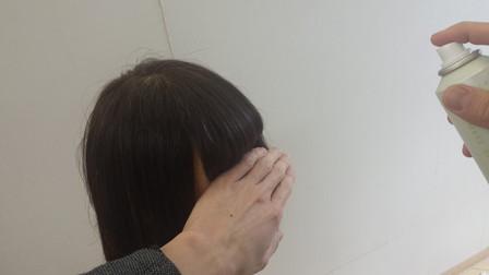 前髪にスプレーがつかないように手で防いでいる写真