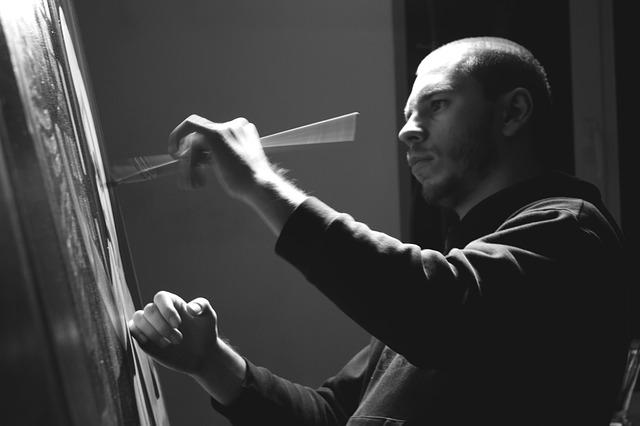 キャンバスに絵を書く男性の写真