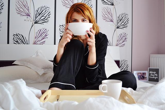 ベッドで食事する女性の写真