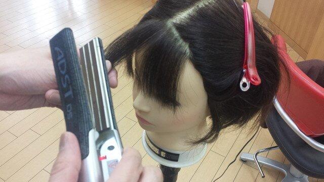 ストレートアイロンで前髪を巻く写真