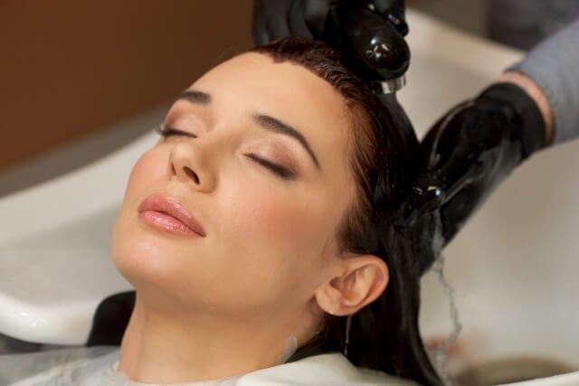 お湯で頭を流す女性の写真