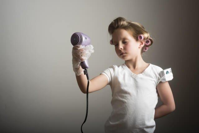 ドライヤーで髪を乾かす女の子の写真