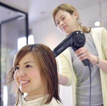 美容師がドライヤーで髪を乾かしている写真
