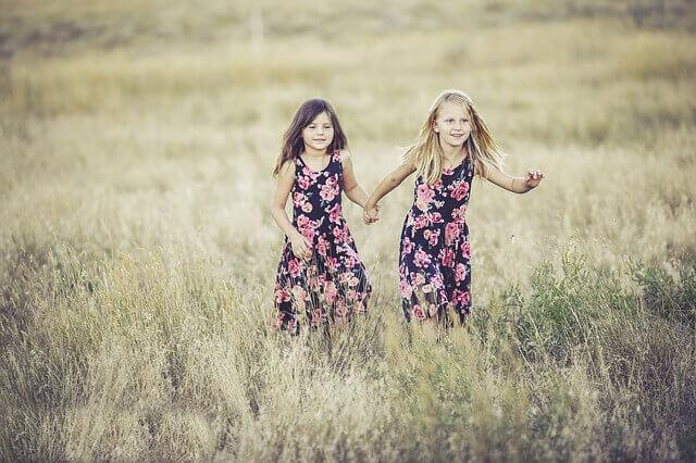 草原を走る2人の子供の写真