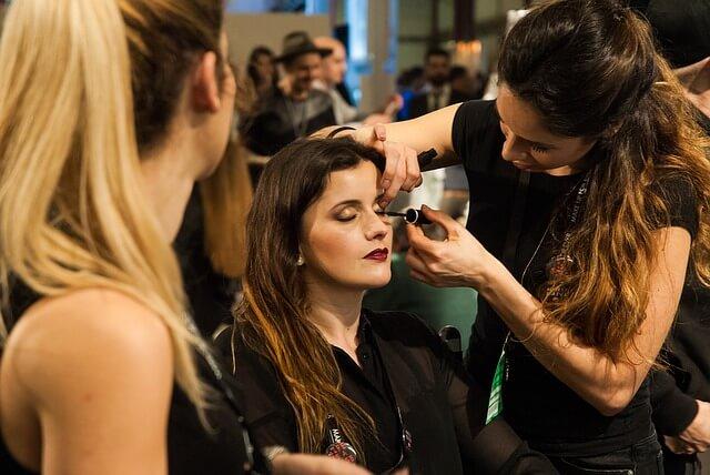 撮影の前にヘアメイクする女性の写真