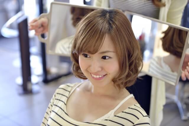 髪型の仕上がりのチェックする女性の写真