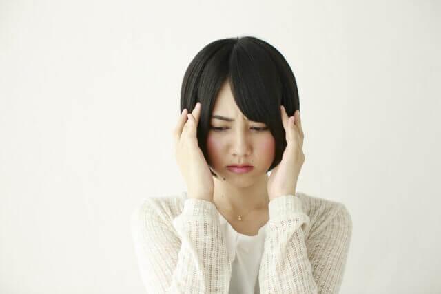 頭に手を当てて困る女性の写真