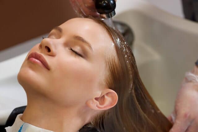 シャワーで頭を流す女性の写真