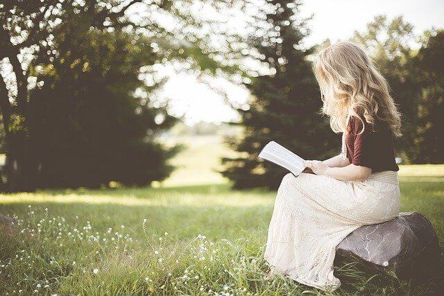 本を読む明るい髪の女性