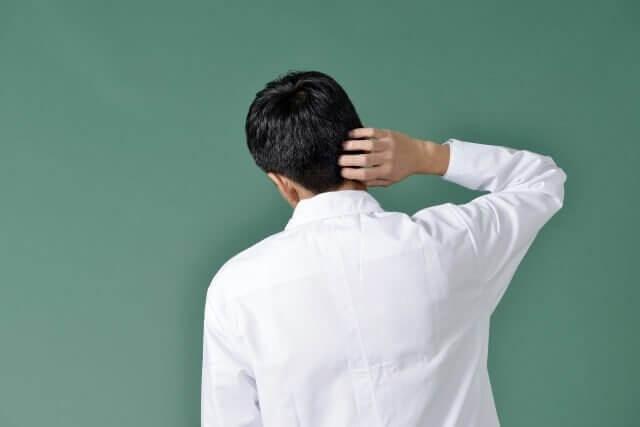 頭をかく男性の写真
