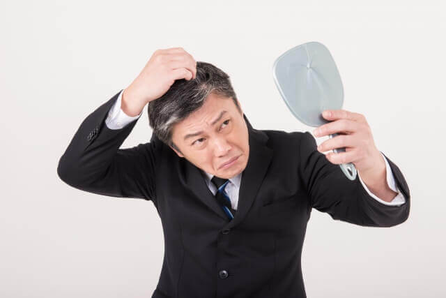 抜け毛を気にする男性の写真