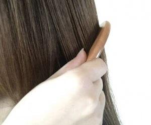 ツゲグシで髪を梳かす女性の写真