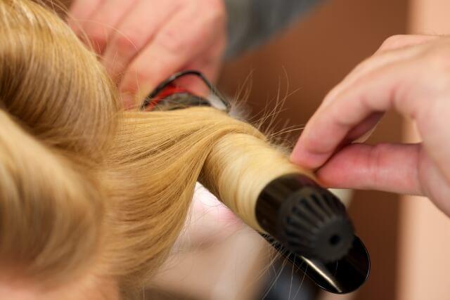 女性の髪の毛をコテで巻いている写真