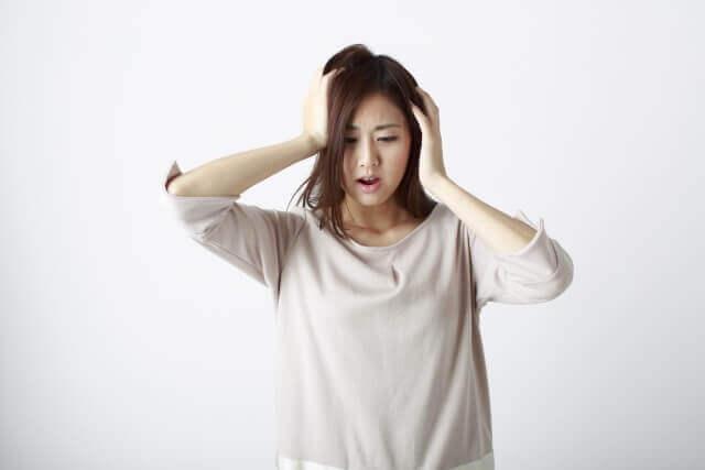 頭に手を当て悩む女性の写真