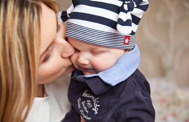 赤ちゃんにキスするお母さんの写真