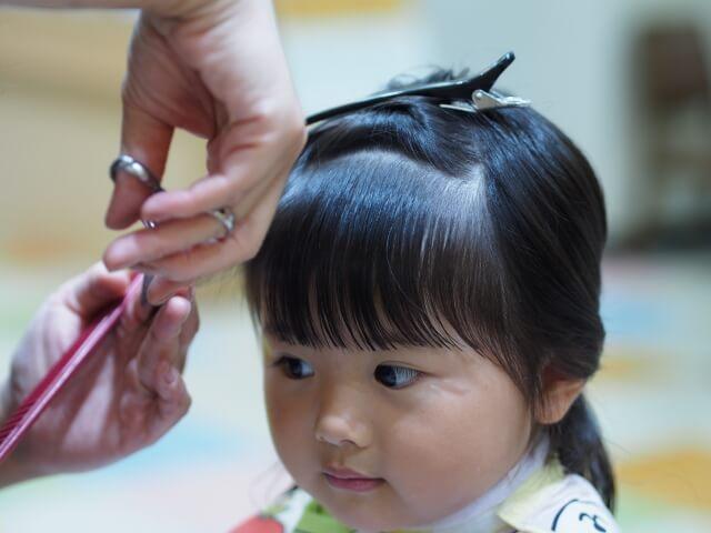 前髪をカットされる女の子の写真