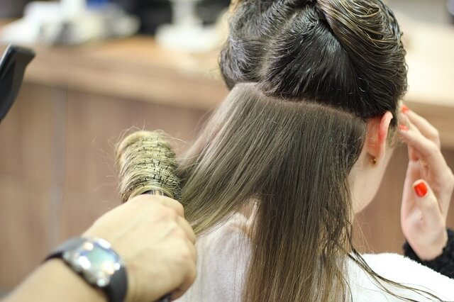 美容師にブローされている女性の写真
