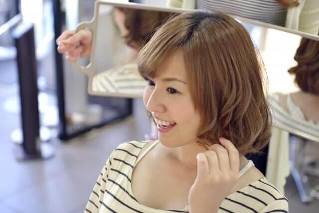 髪型の仕上がりを確認する女性の写真