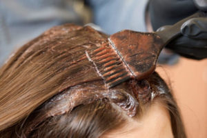 根元をヘアカラーする女性の写真
