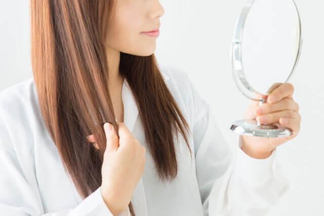 髪の毛をチェックする女性の写真