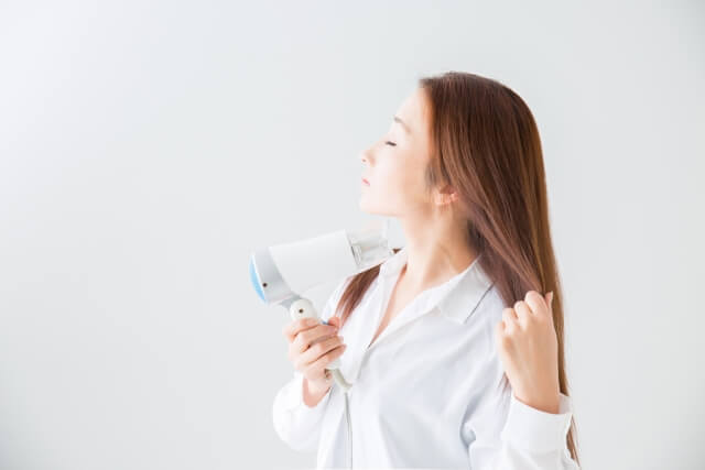 ドライヤーで髪の毛を乾かす女性の写真