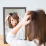 髪の毛に困る女性の写真