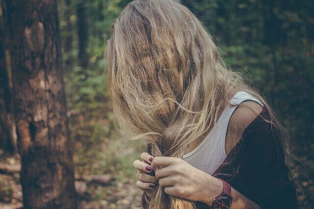 髪の毛の傷みを気にする女性の写真