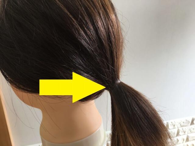 ヘアゴムで結んでいる髪の毛の写真矢印