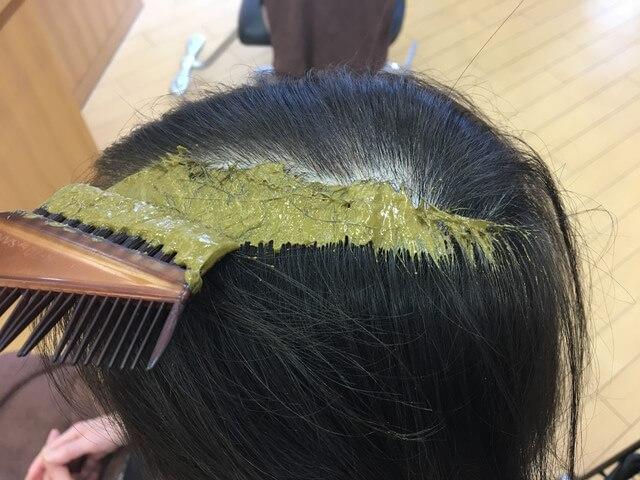 ヘナを髪の毛にぬっているところの写真