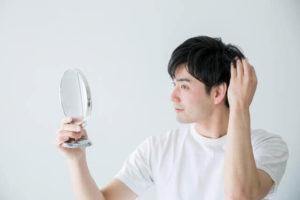 髪の毛を気にしている男性の写真
