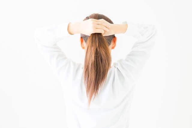 髪を結ぶ女性の写真