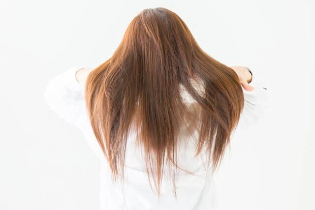 髪の毛をかき上げる女性の写真